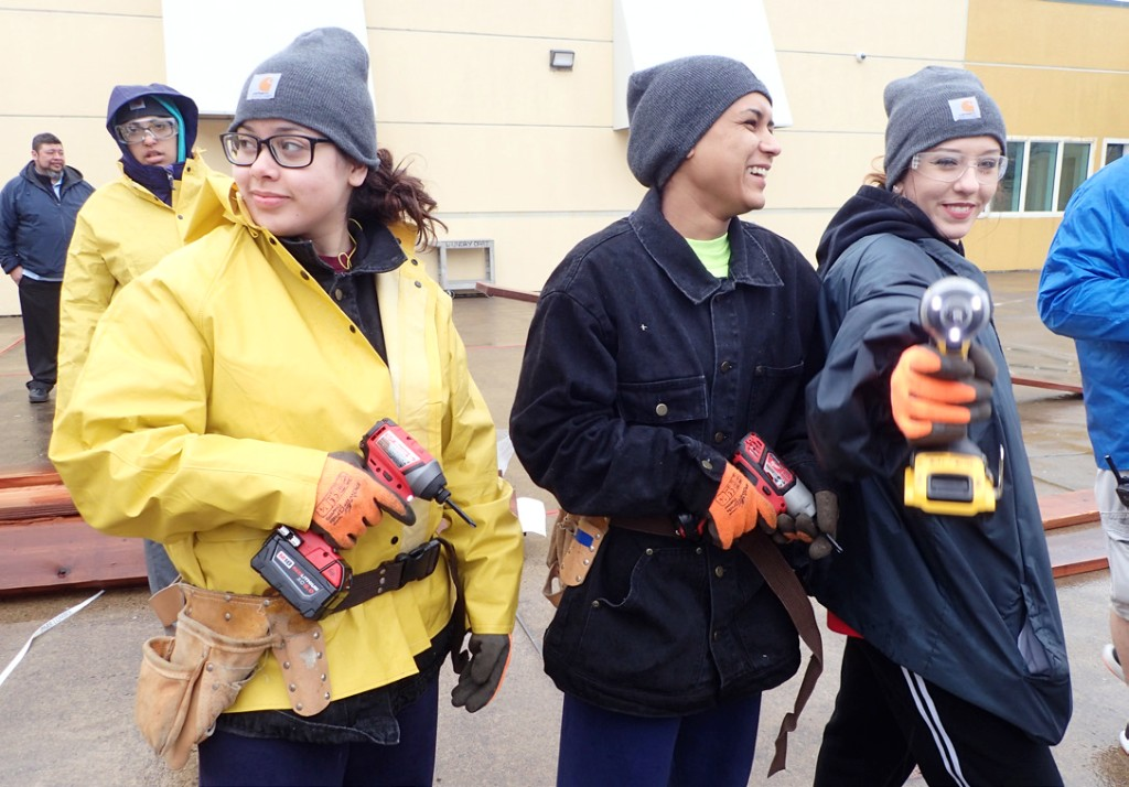 Students holding electric drills