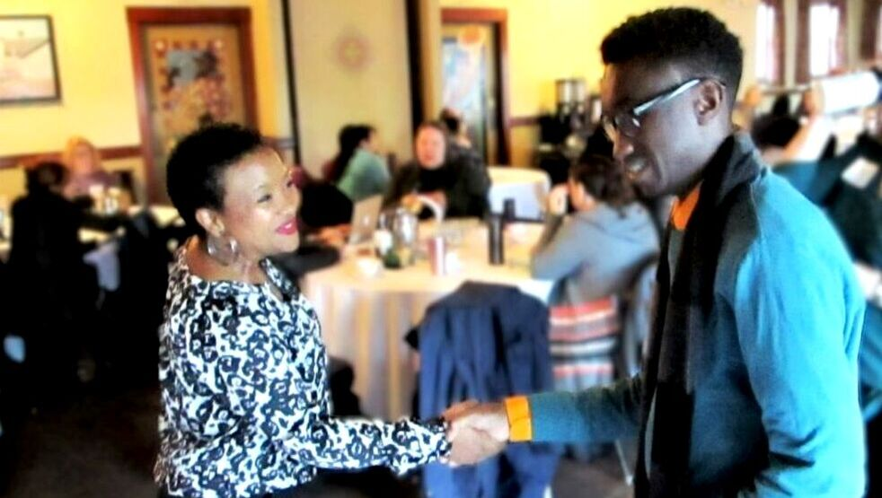 Presenter Robinson shakes the hand of an attendee